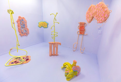 "Danni O'Brien, ""Tongue Puddles"". 2019, 11' x 15' x 10, mixed media sculptural installation; found objects, hand-tied latch hook rugs, glazed ceramics, homemade paper pulp. Courtesy of the artist."